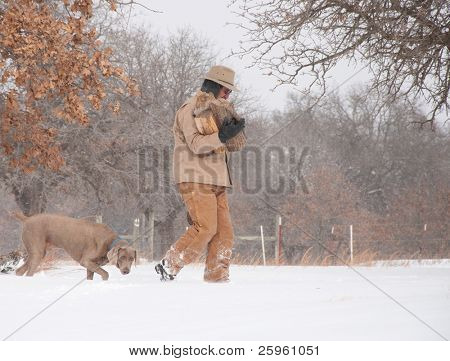 Man carrying firewood bundled up in warm winter clothes, with his dog following in heavy snow fall