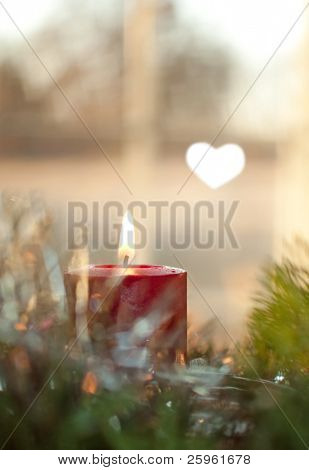 Red Christmas candle burning, surrounded by a wreath and decoration, against a window, with a bokeh heart