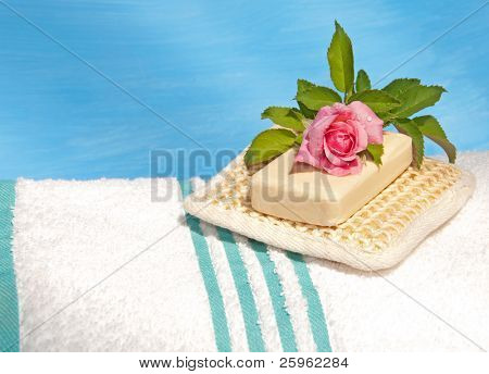 White bath towel with an exfoliation pad, soap and a delicate pink rose