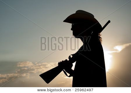 Silhouette of a young man in a cowboy hat with a shotgun on his shoulder