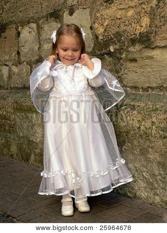 Menina de vestido de baptizado de salto. Suave rosto focalizado