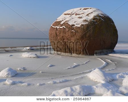 Big stone at sea in winter