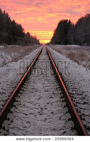 Amazing rural winter scene in sunset with railroad