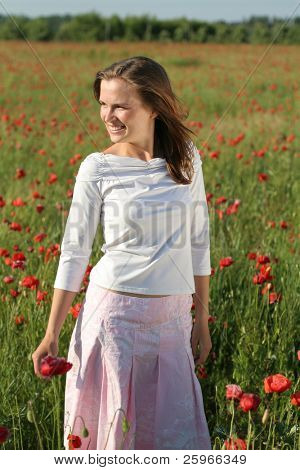 Girl stands in poppy field in nice summer day