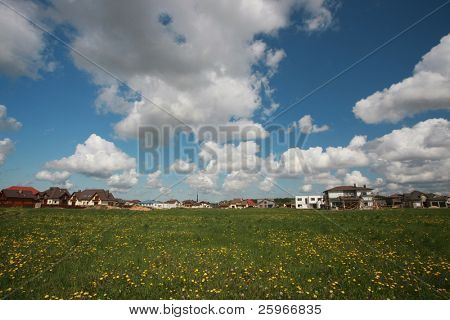 Village from new houses in nice spring day - dandelion field and clouds
