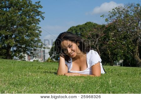 Pregnant young mum on a grass in park