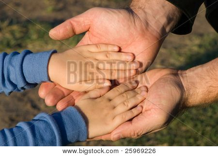 Hands of the child laying on hands of the father