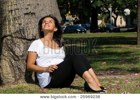 Pregnant young mum dreaming, sitting near a tree in park