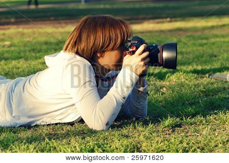 professional woman photographer in park on a grass.Cross effect