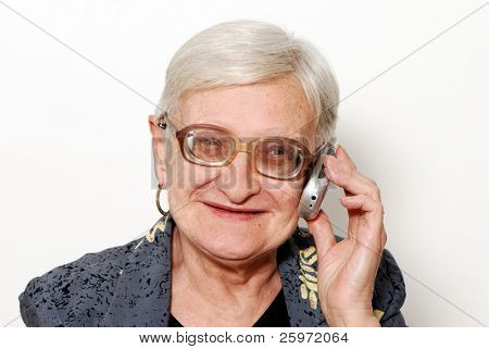 Portrait of the old woman with a mobile phone on a light background