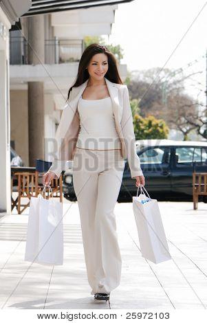 Das schöne junge Mädchen mit einer Einkaufstasche