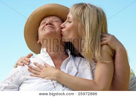 The daughter kissing  mother outdoors