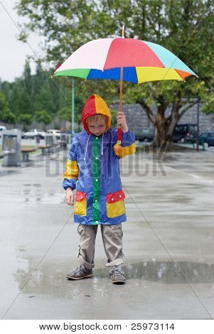 The boy with an umbrella standing under a rain