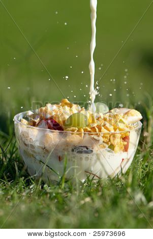 Milk stream flowing in a bowl with fruit and corn-flakes