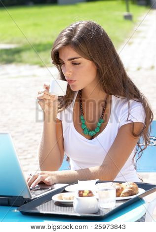 The young Argentina girl with  laptop drinking coffee outdoors