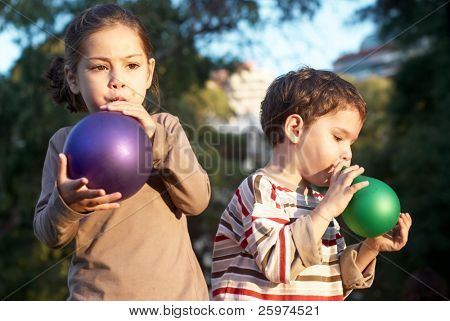 children inflating balloons in park