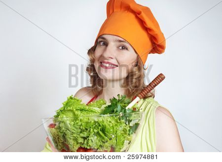 The beautiful cook with green salad in hands