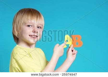The small schoolboy with letters on a blue background