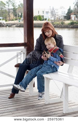 Mother with the son sitting on a bench in arbours on the bank of lake