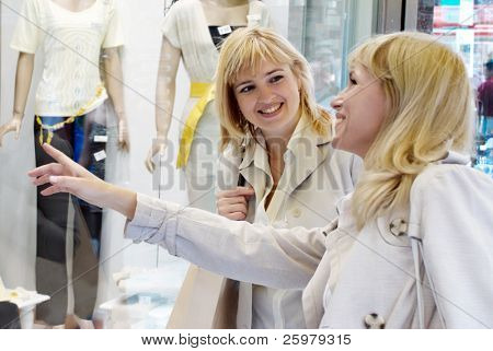 Two young women near a show-window of shop of clothes
