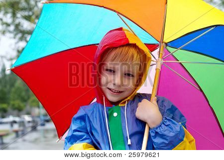 The boy with an umbrella standing under a rain