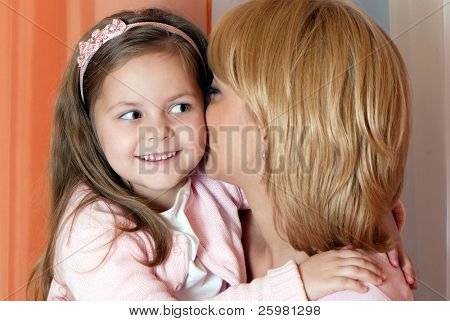 Portrait mother with is whispering with her little girl