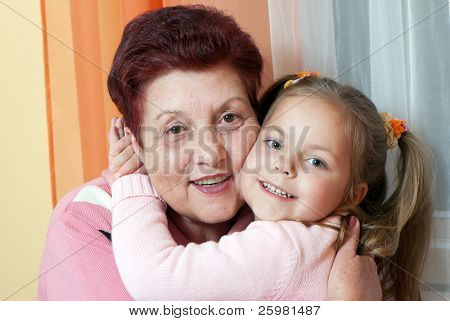 Closeup portrait of a grand daughter and grandmother smiling