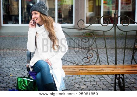 Young smiling woman sitting on berm calling with mobile phone