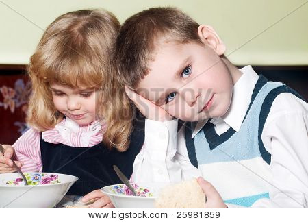 two kids sitting at table during a dinner  in a kindergarten