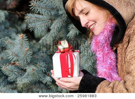 Beauty young girl with christmas gift in park