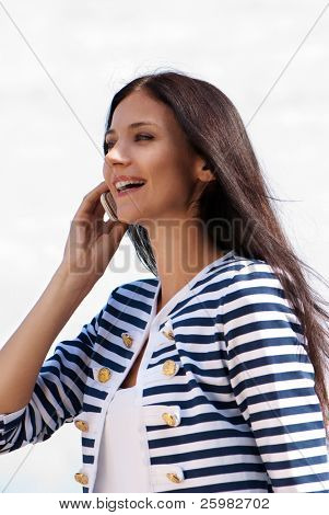 Closeup portrait of a smiling young beautiful woman talking on cellphone