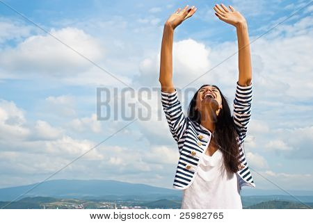 Portrait of smiling young woman lifted hands to sky