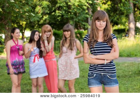 Upset teenage girl with friends gossiping in park