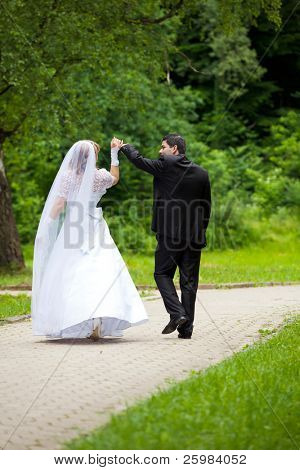 dancing wedding couple at a park on a sunny day