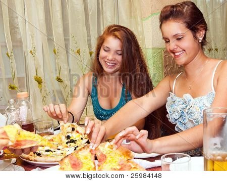 teenagers eating pizza in restaurant