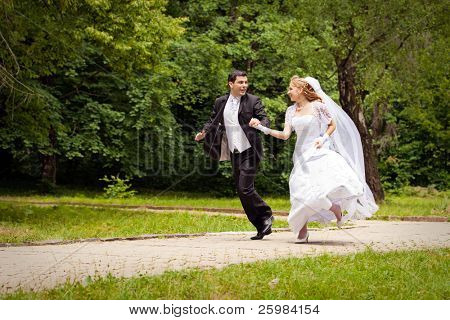 happy bride and bridegroom running along the alley in the park