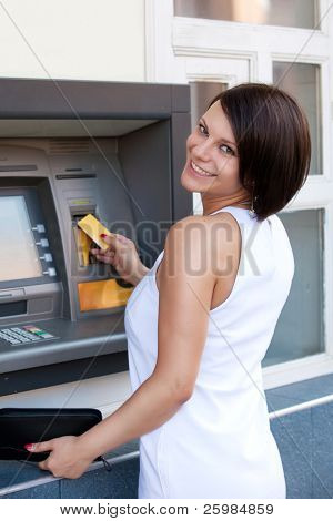 Woman withdrawing money from credit card at ATM