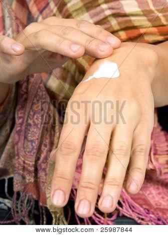 Impede a mulher colocar creme nas mãos
