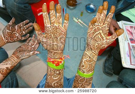 An artist is applying a traditional henna tattoo to woman's hand
