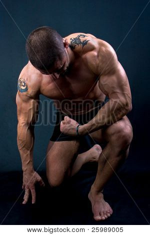 The Perfect muscular man posing isolated on black background