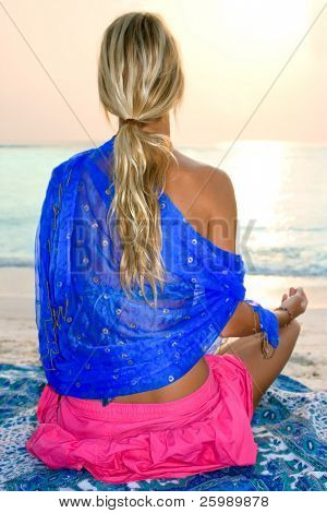 woman meditating on tropical beach in sunrise