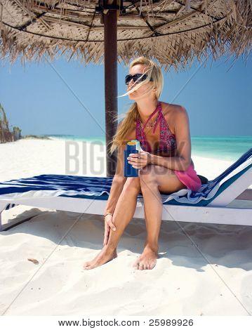 beautiful woman applying suntan lotion at a tropical beach