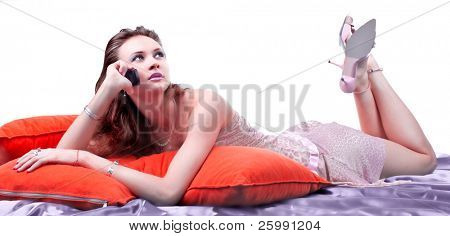 Beautiful young women is resting on the pillows and talking over the phone