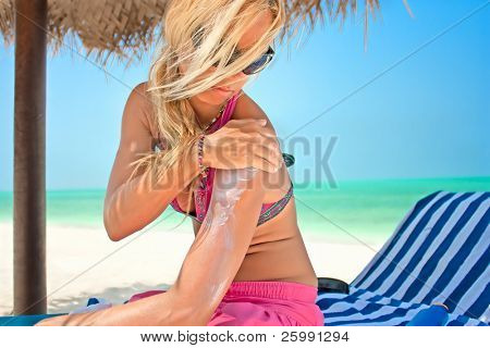 Beautiful woman applying suntan lotion at a tropical beach