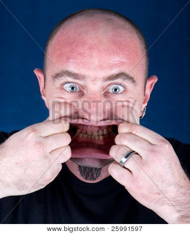 Man stretching his mouth to make a funny face, studio shot