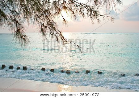 Soft light of sunrise on tropical beach with two fisher-mans