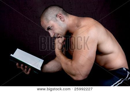 Young attractive male bodybuilder reading the book, pensive pose . Studio shot, dark background.
