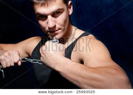 Young muscular man with a chain isolated on dark blue, studio shot