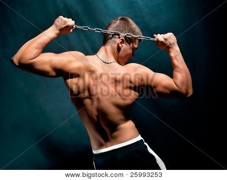 Young muscular man with a chain isolated on dark, studio shot