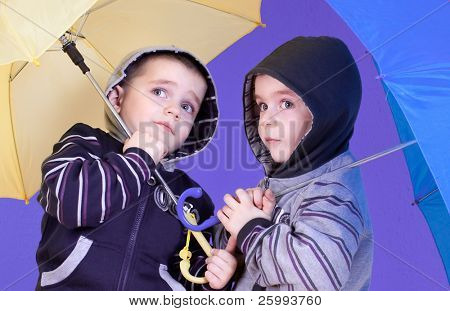 Close up twins brother  have fun under an umbrellas, studio shot